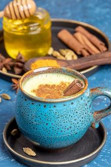 Blauwe kop van traditionele indiase ayurvedische gouden kurkuma latte melk met ingrediënten op blauwe achtergrond. selectieve aandacht.