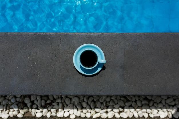 Blauwe kop warme koffie naast het zwembad
