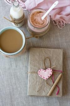 Blauwe kopje koffie in gebreide trui, zelfgemaakte bessen yoghurt, vintage notebook voor records in een fles met melk