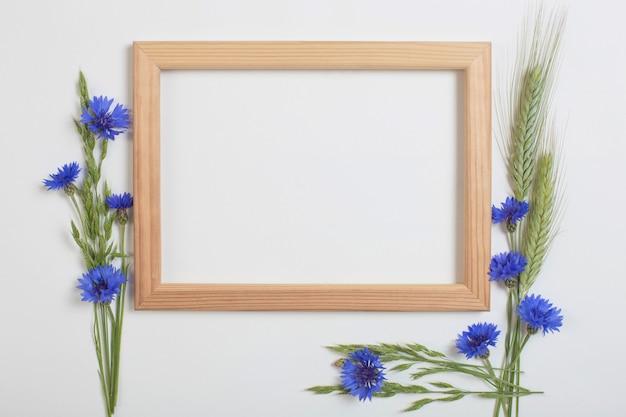 Blauwe korenbloemen en granen met houten frame