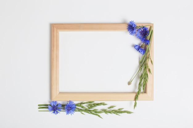 Blauwe korenbloemen en houten frame op witte ondergrond