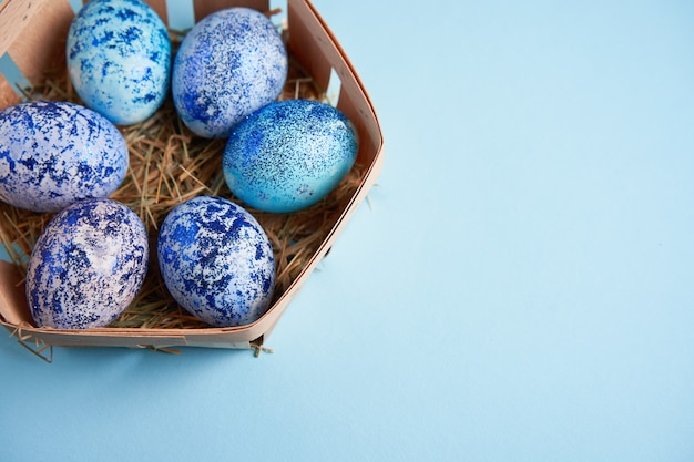 Blauwe kosmoskippeneieren liggen in ronde houten mand die op een blauwe achtergrond staat.