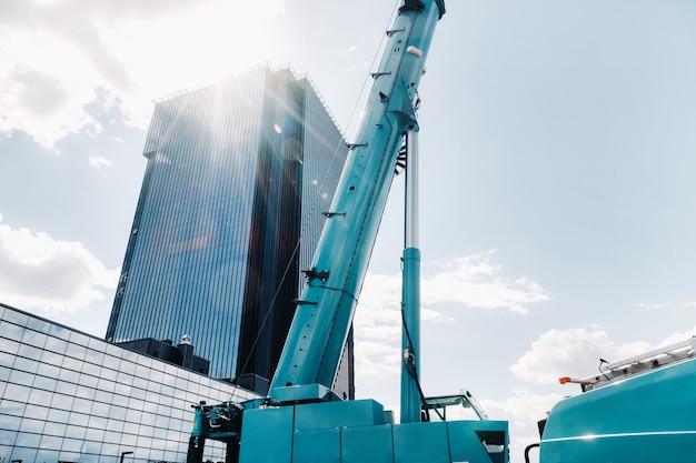 Blauwe kraan hefmechanisme met haken in de buurt van het moderne glazen gebouw,