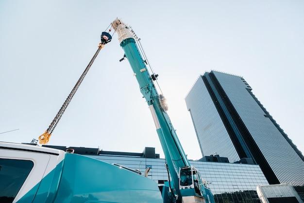 Blauwe kraan hijsmechanisme met haken in de buurt van het moderne glazen gebouw