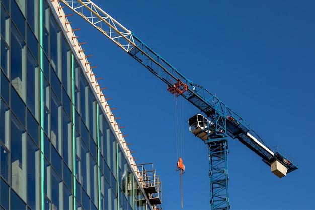 Blauwe kraan op een bouwplaats tegen een blauwe hemel bouw van een commercieel onroerend goed groot glasoppervlak van de gevel