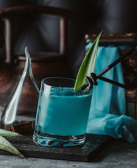 Blauwe lagune in een glas met ananasbladeren en zwarte rietjes