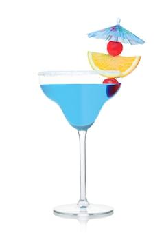 Blauwe lagune zomercocktail in margarita glas met sinaasappelschijfje en zoete kers met paraplu op witte achtergrond.