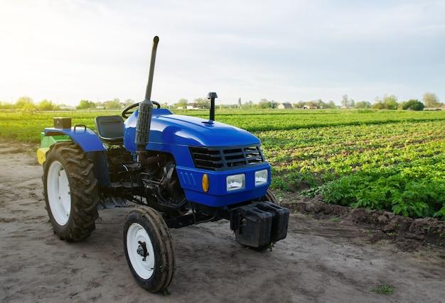 Blauwe landbouwtractor staat op veldtoepassing van landbouwmachines bij het oogsten