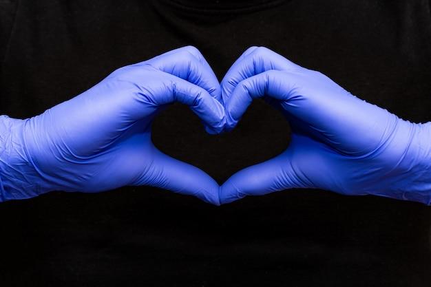 Blauwe latex handschoenen voor medische bescherming in hartvorm symbool, ondersteunen de dokters en verpleegsters, covid-19, coronavirus. zwarte muur
