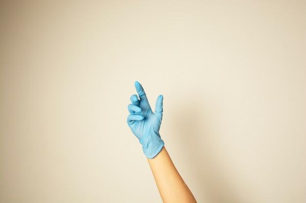Blauwe latex medische handschoenen op een vrouwelijke hand die met exemplaarruimte wordt geïsoleerd.