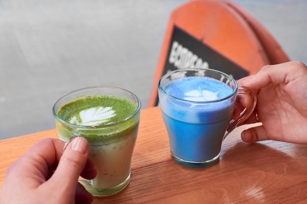 Blauwe latte en groene latte in twee vrouwelijke handen. vrienden ontmoeten elkaar in een café bij het raam. trendy variaties, alternatief voor koffie, in trendy glazen bekers. bordteken buiten, exemplaar-ruimte.