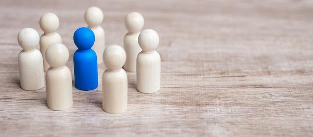 Blauwe leiderszakenman met cirkel van houten mensen. leiderschap, business, team en teamwork