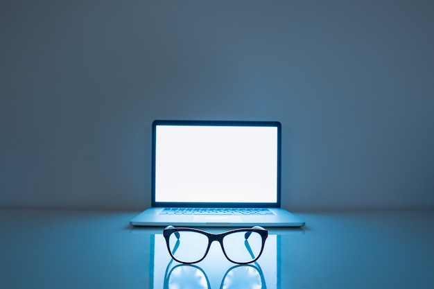 Blauwe lichte blokkers en laptop op donkere achtergrond