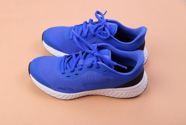 Blauwe loopschoenen op roze pastel achtergrond