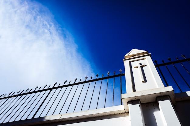 Blauwe lucht achter een witte muur met een hek met een religieus kruis