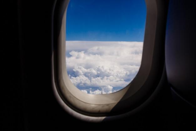 Blauwe lucht en wolk met uitkijken uit een vliegtuig patrijspoort raam tijdens een vlucht