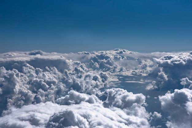 Blauwe lucht en wolken achtergrond vanuit vliegtuig raam uitzicht