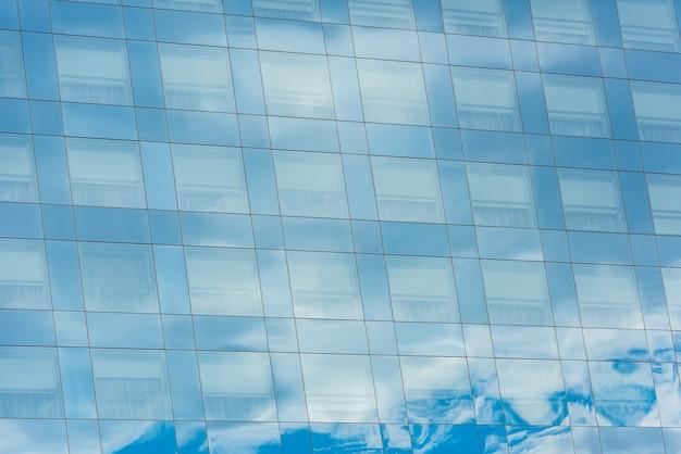 Blauwe lucht en wolken weerspiegeld in ramen van modern kantoorgebouw