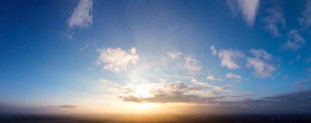 Blauwe lucht en zonsondergang, kleine wolken rond de zon.