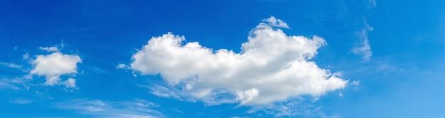 Blauwe lucht met licht krullende wolken, panorama
