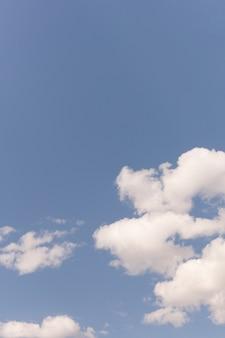 Blauwe lucht met witte drijvende wolken