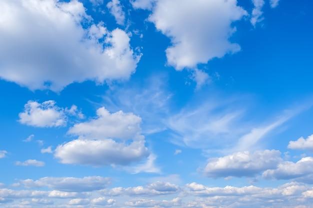 Blauwe lucht met witte pluizige wolkenachtergrond
