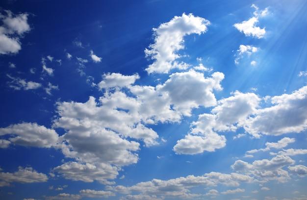 Blauwe lucht met witte wolken in de stralen van de felle zon