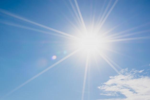 Blauwe lucht met wolken en zon reflectie