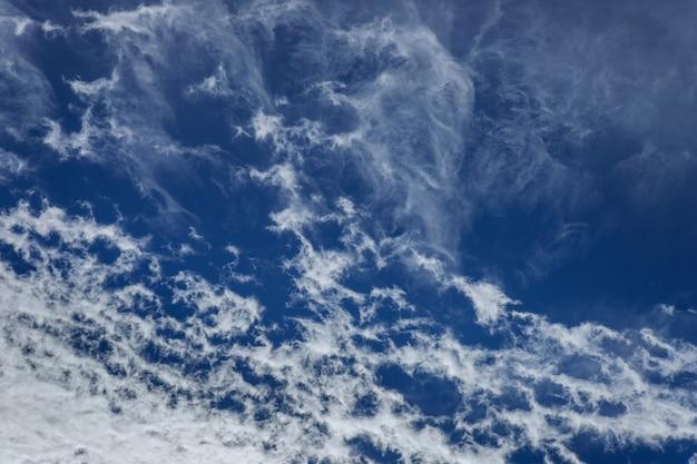 Blauwe lucht met wolken en zon.
