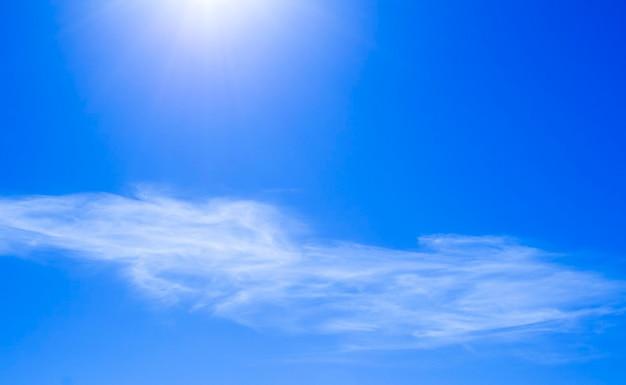 Blauwe lucht met zon en wolken