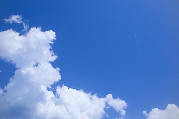 Blauwe lucht, witte wolken en spoor van vliegtuig