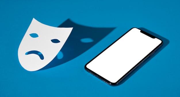 Blauwe maandag met droevig masker en smartphone