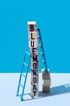 Blauwe maandag met houten kubussen en ladders