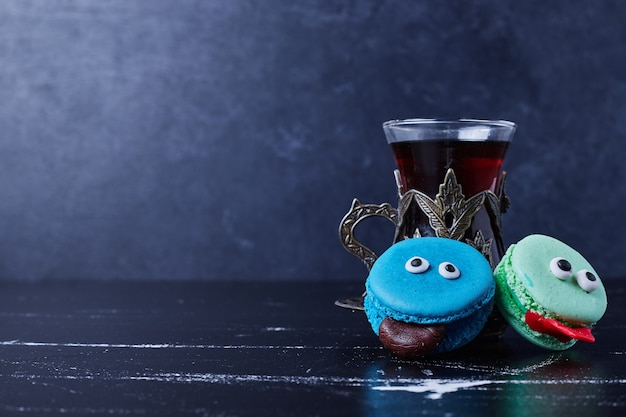 Blauwe macarons met een glas thee.