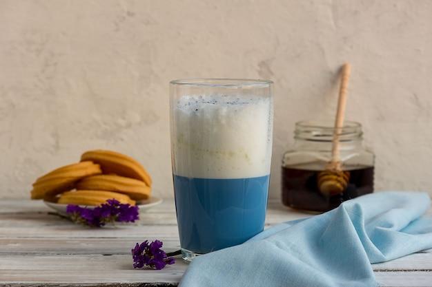 Blauwe matcha thee in een glas latte op tafel.