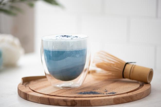 Blauwe matcha thee met latte schuim in een glas