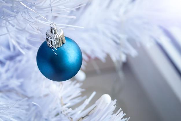 Blauwe matte bal op een witte kunstmatige kerstboom met kopie ruimte