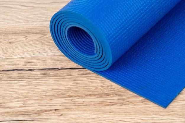 Blauwe matten voor fitnes spelen in het huis op houten vloeren.