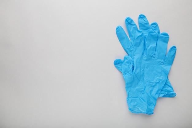 Blauwe medische handschoenen op een grijze achtergrond