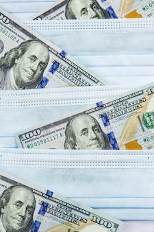 Blauwe medische maskers en dollars. financiële crisis door coronavirus, contante betalingen aan artsen, dure ziekenhuisdiensten, sponsoring van medisch onderzoek.