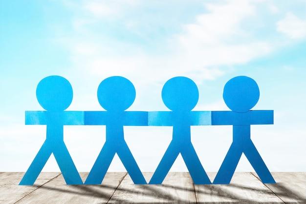 Blauwe mensen papier hand in hand staan met een blauwe hemelachtergrond. wereldbevolkingsdag concept