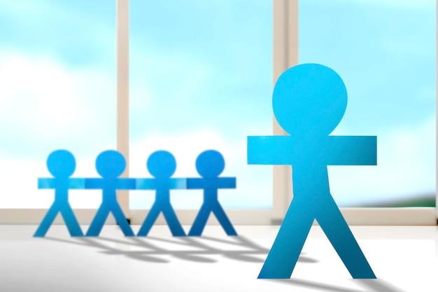 Blauwe mensen papier hand in hand staande met de achtergrond van het venster. wereldbevolkingsdag concept