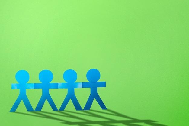 Blauwe mensen papier hand in hand staande met een gekleurde achtergrond. wereldbevolkingsdag concept