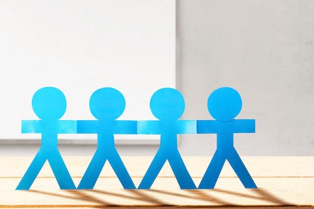 Blauwe mensen papier hand in hand staande met muur en raam achtergrond. wereldbevolkingsdag concept