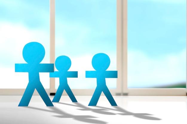 Blauwe mensen papier staan met de achtergrond van het venster. wereldbevolkingsdag concept