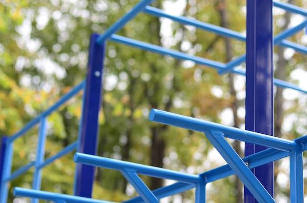 Blauwe metaalpijpen en dwarsbalken tegen een straatsportterrein voor opleiding in atletiek