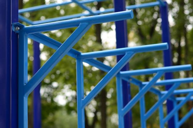 Blauwe metalen buizen en dwarsbalken tegen een straat sportveld