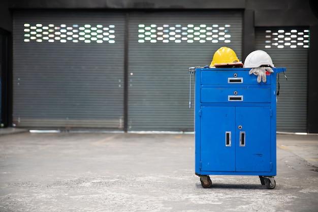 Blauwe metalen gereedschapskast met veiligheidshelmen, handschoen, documentenblok op de kast met garage achtergrond. reparatie van auto's.