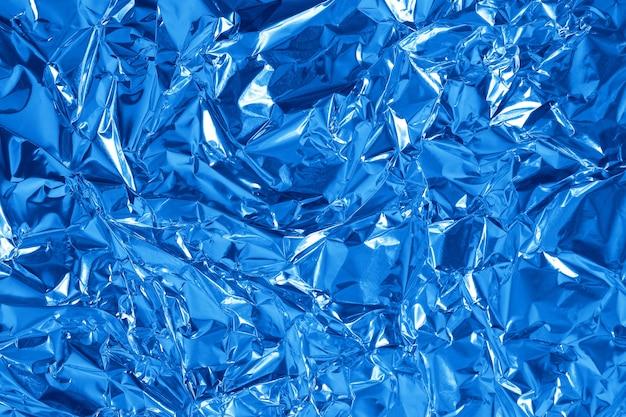 Blauwe metallic folie blad glanzende textuur achtergrond, verfrommeld inpakpapier.
