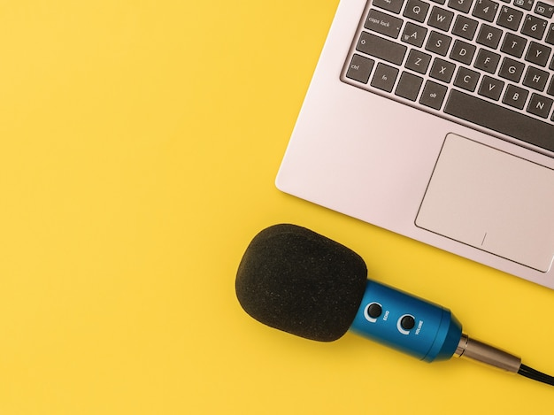 Blauwe microfoon aangesloten op een laptopcomputer op een gele achtergrond. het concept van werkplekorganisatie. apparatuur voor het opnemen, communiceren en luisteren naar muziek.